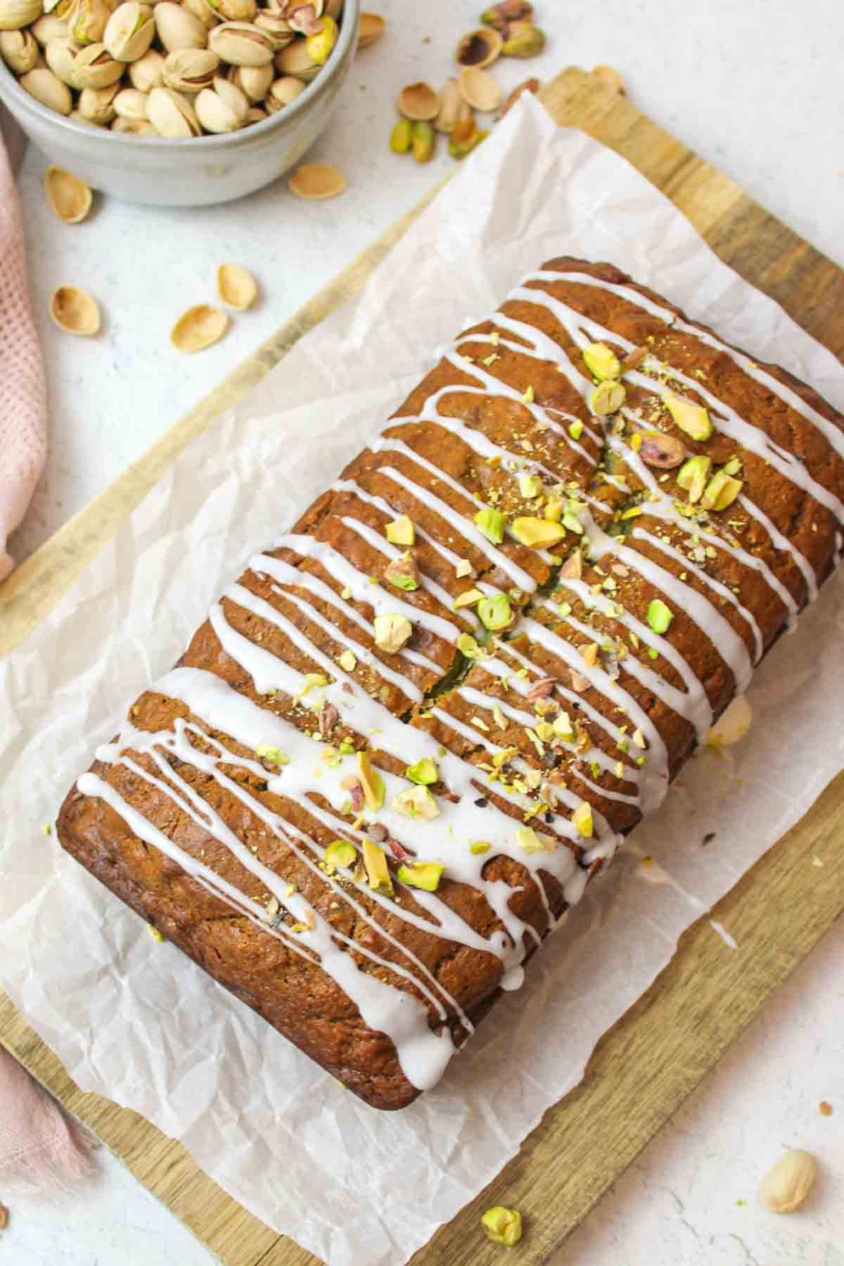 a thickly sliced loaf of pistachio banana bread next to a box of pistachio pudding