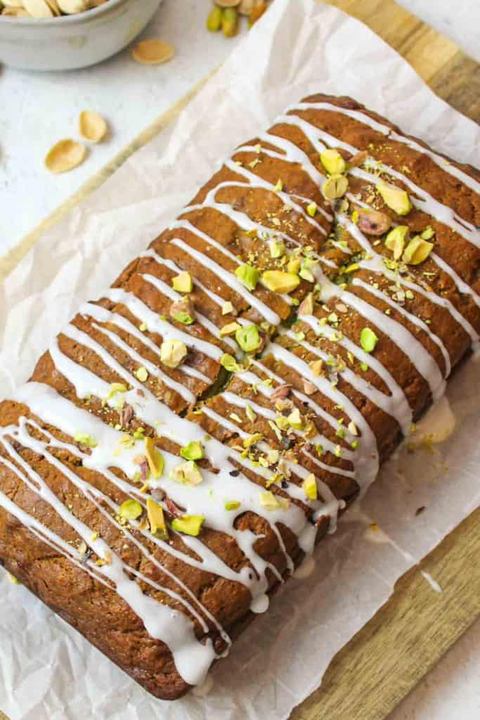 a loaf of sliced pistachio banana bread with bread slices and boxed pudding in background