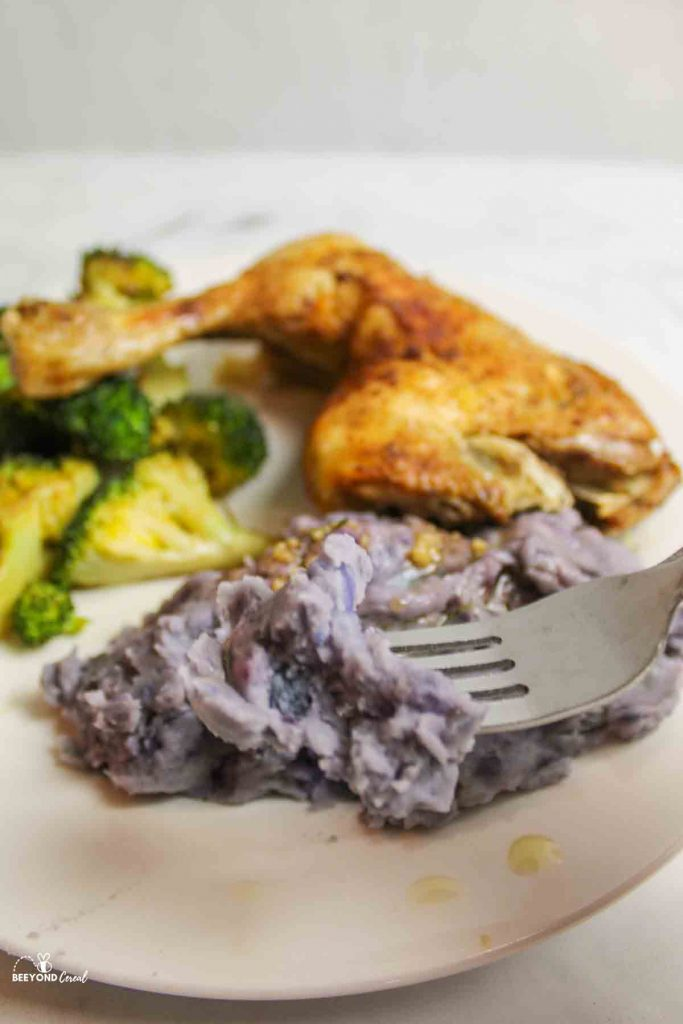a fork digging into a biteful of purple mashed potatoes