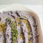 fresh thyme on browned butter and garlic purple mashed potatoes in white baking dish