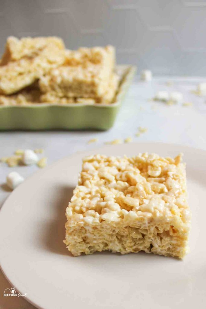 coconut oil rice krispies in a dish in background with a slice in front
