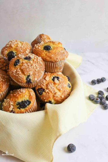 an angled view of a towel lined basket filled with blueberry muffins and scatered blueberries around it