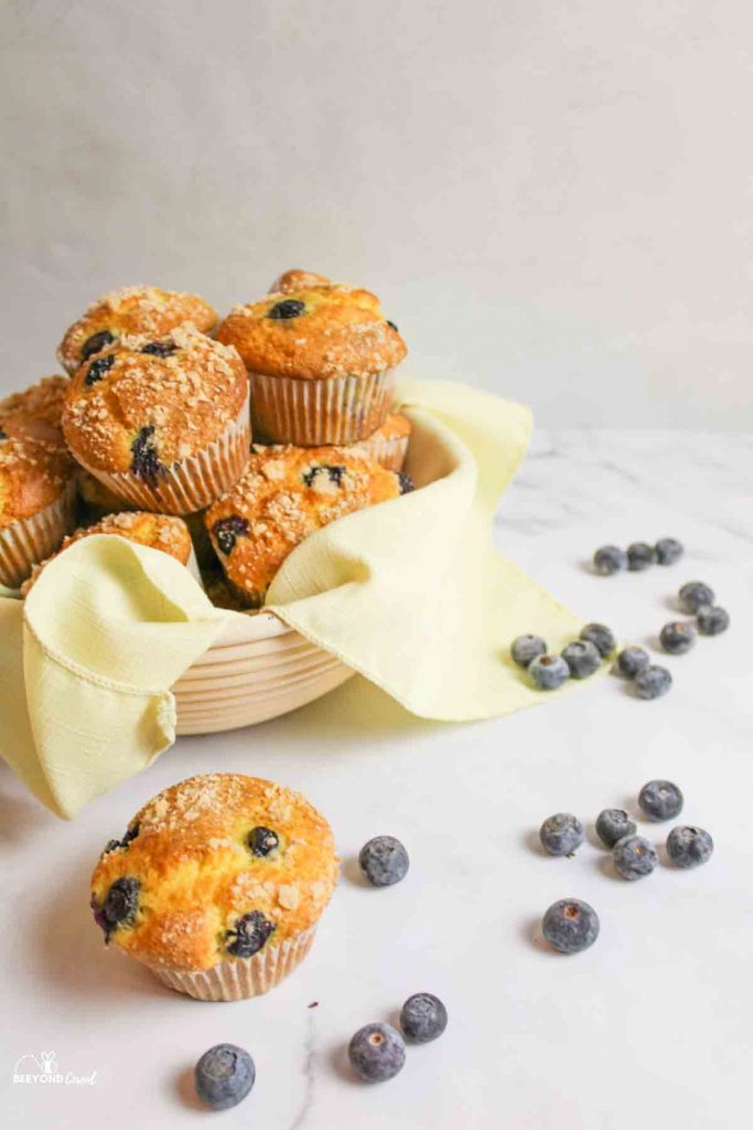 a basket full of muffins with a muffin and scattered blueberries in front
