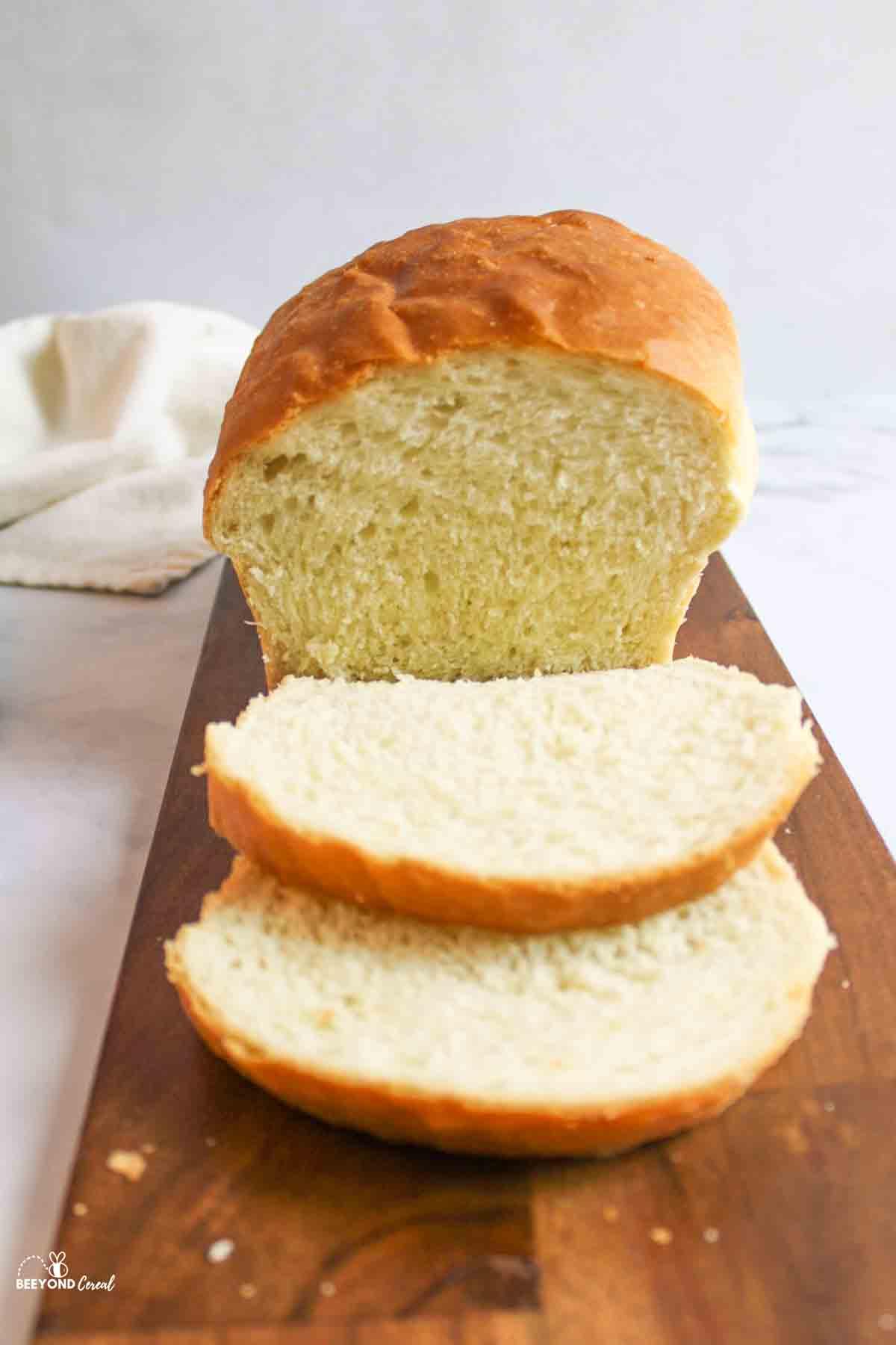 a sliced loaf of white bread on a dark wood cutting board