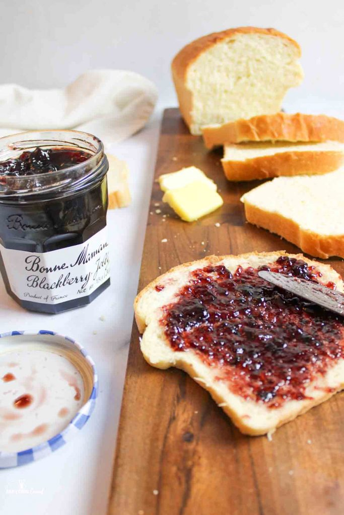 jelly being spread onto a slice of white bread with open jelly jar and sliced bread to the sides