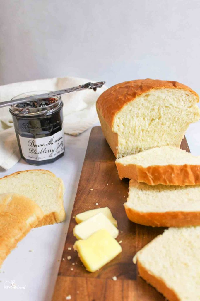 a sliced loaf of white bread next to pads of butter and a jar of jelly with used knife
