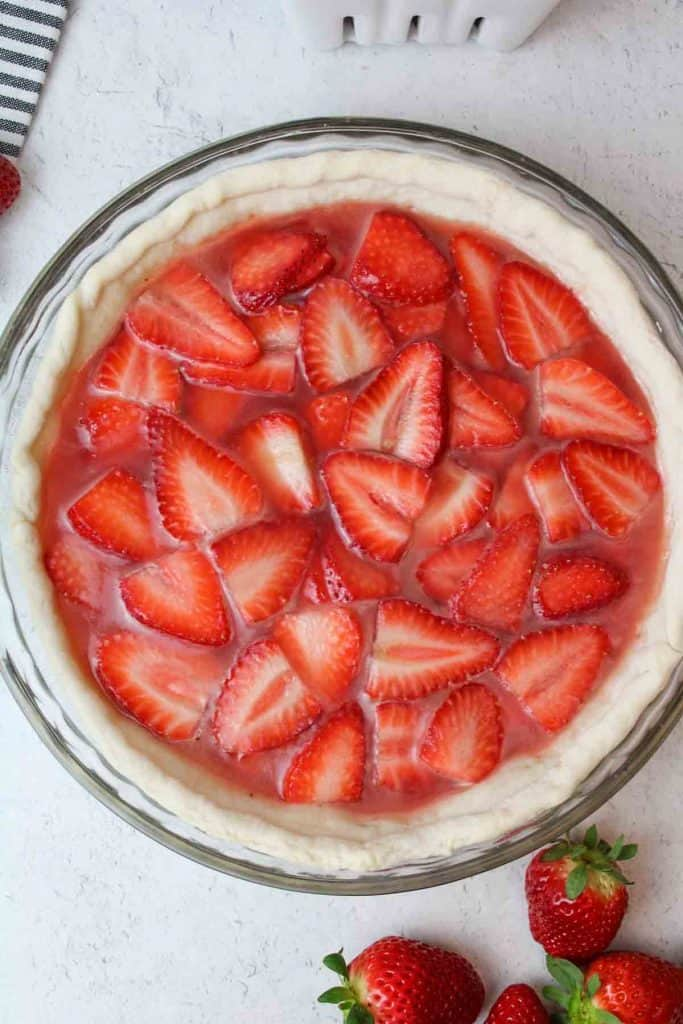 a whole strawberry pie next to a plate with a fork and some fresh strawberries to the side