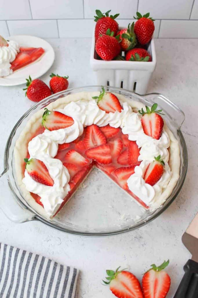 a strawberry pie with whipped cream missing a slice