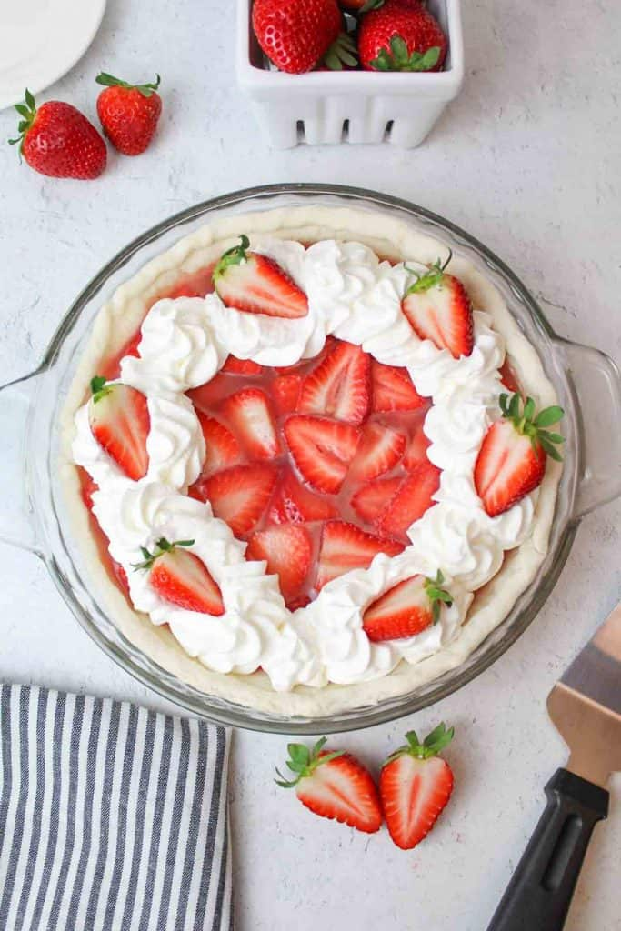an upclose view of a whipped cream topped strawberry pie