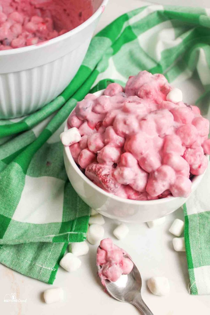 heaven berry fluff salad in a bowl with a used spoon and scattered marshmallows around it