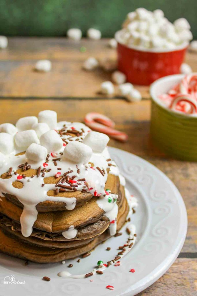 stacked hot cocoa pancakes on a plate with marshmallows, sprinkles, and candy canes