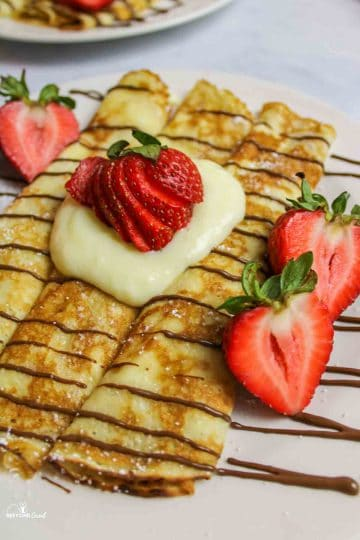 up close view of pancake mix crepes rolled on a plate with custard and fresh strawberries