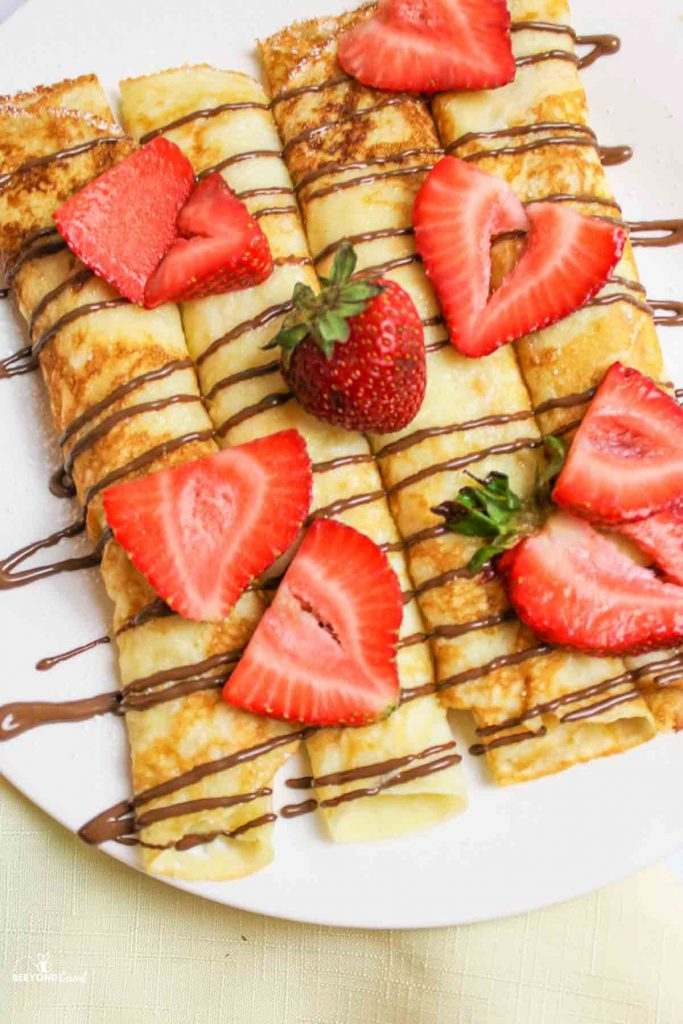 aerial view of crepes on a plate with chocolate drizzle and fresh strawberries