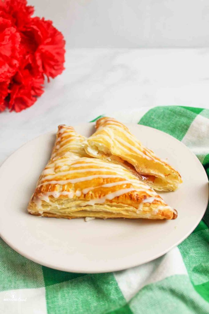 strawberry cream cheese turnovers on a white plate on a green checkered towel with red flowers in background