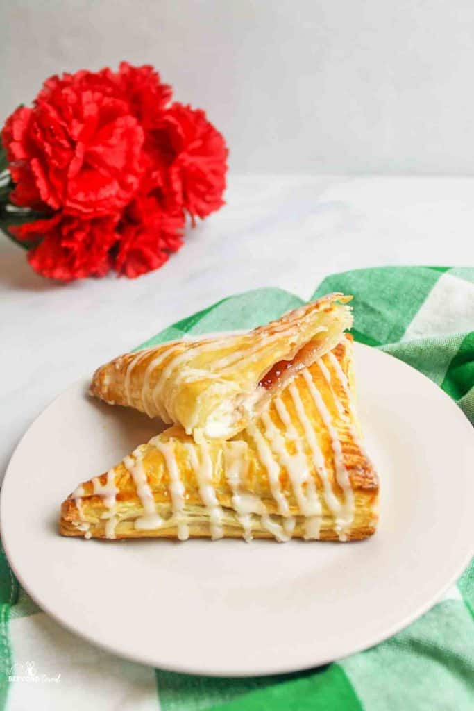 one and a half stacked strawberry cream cheese turnovers on a white plate with red flowers in background
