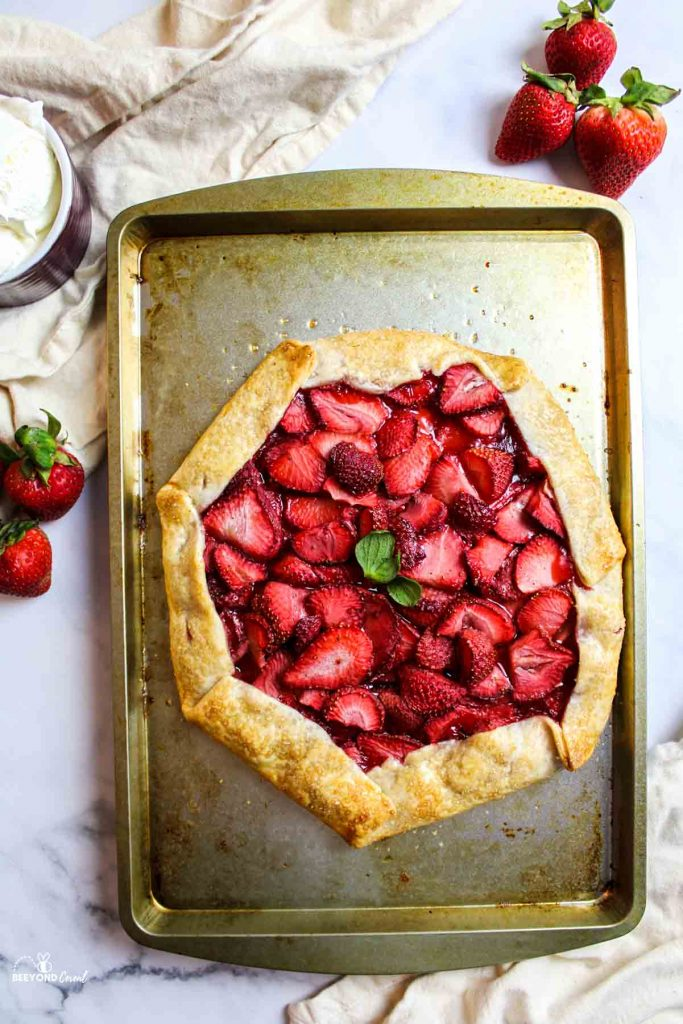 aerial view of strawberry galette on a baking sheet with fresh berries, cream, and kitchen towel around it