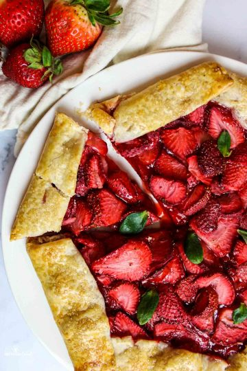 aerial view of a sliced strawberry galette next to fresh strawberries