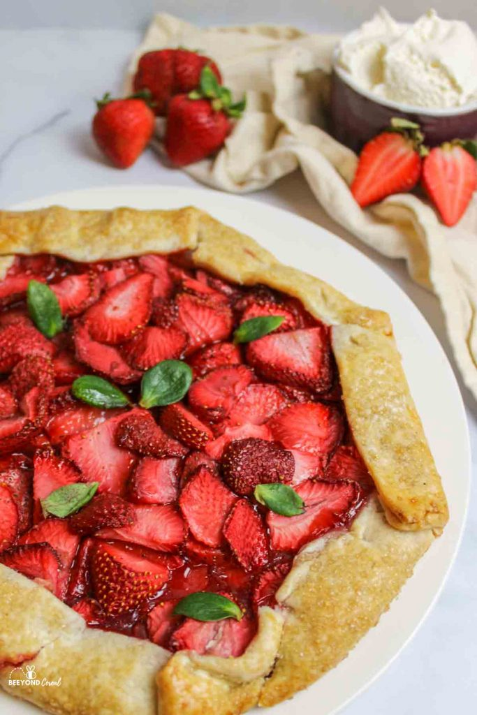 a strawberry galette on a white plate with fresh strawberries and whipped cream in background