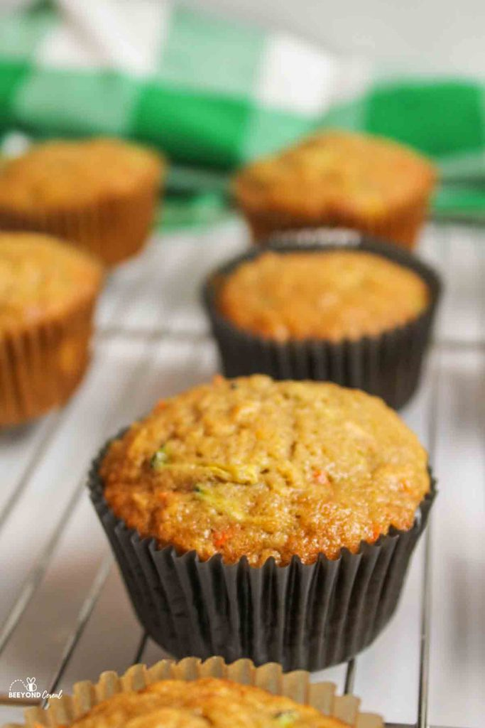 a close up of a zucchini carrot oatmeal muffins on a wire rack