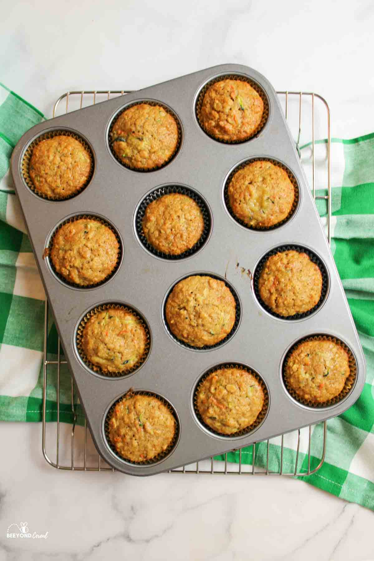 zucchini carrot oatmeal muffins in a baking tray on a wire rack and towel