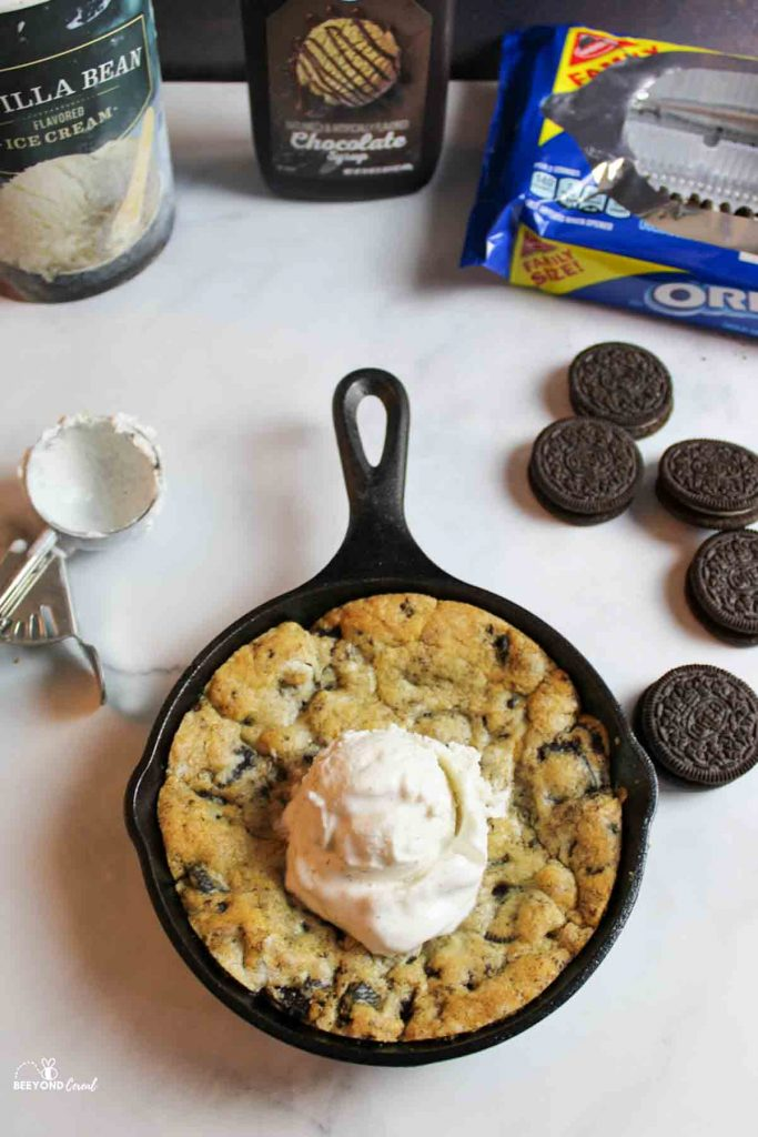 an oreo pizookie in a cast iron skillet with ice cream scoop on top. Use scooper to the side and more food items such as ice cream container, chocolate syrup bottole and oreos in and out of package around the skillet cookie