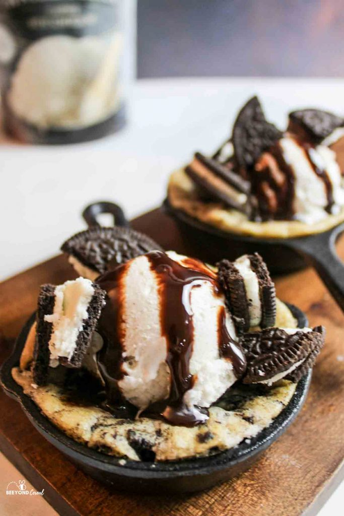 a small cast iron oreo cookie topped with ice cream, chocolate sauce and chopped oreo cookies