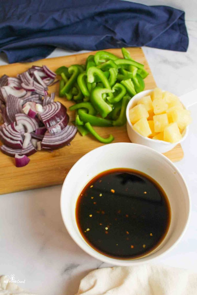 sliced onion, bell pepper, pineapple, and a bowl of teriyaki sauce mix