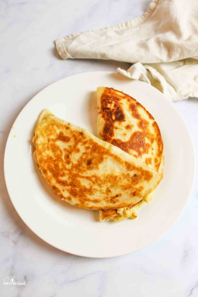 aerial view of two mac and cheese quesadillas on a white plate with towel to the side