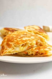 two triangles of mac and cheese quesadillas stacked on a plate with more in background