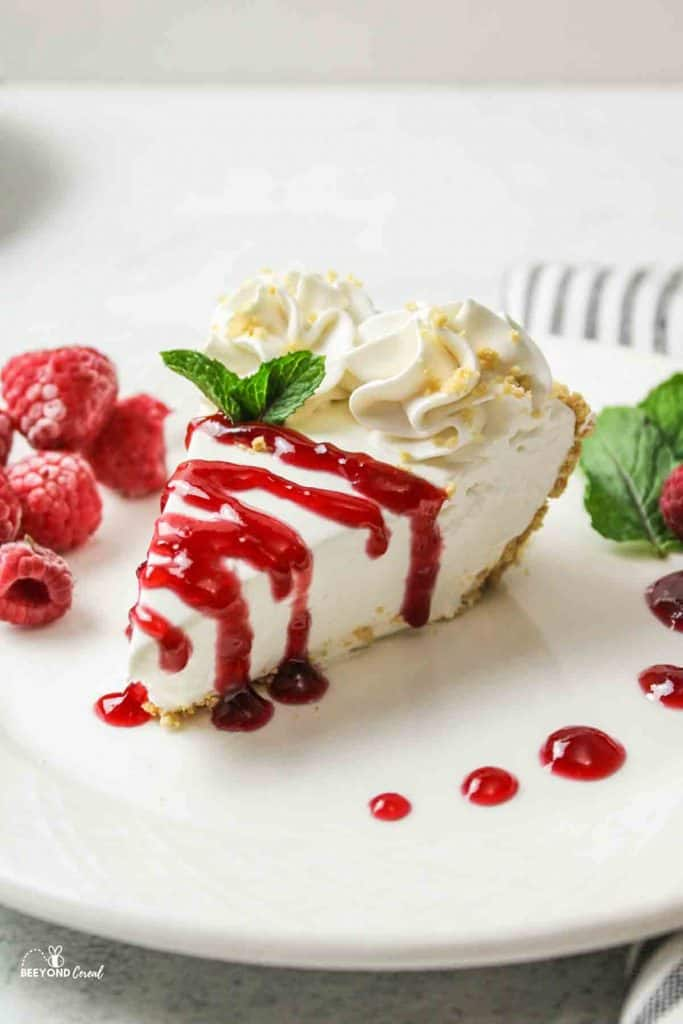 a side view of a sliced no bake cheesecake in a pie plate with strawberry topping