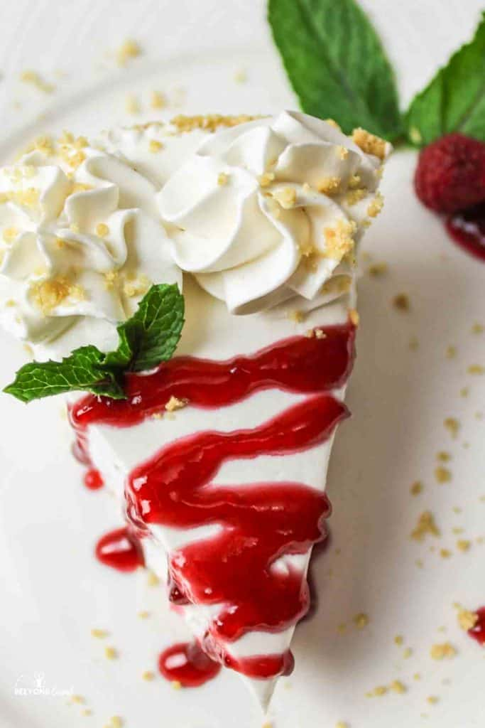 aerial view of sliced no bake cheesecake with strawberry glaze top