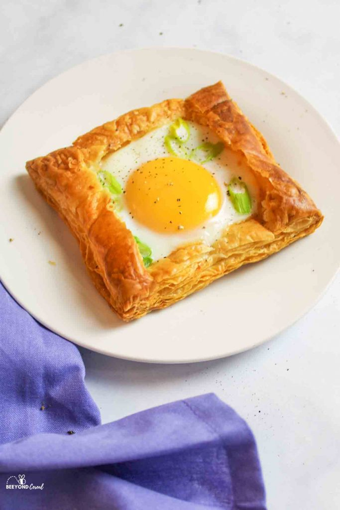 an egg tart on a plate with a sprinkling of fresh ground black pepper