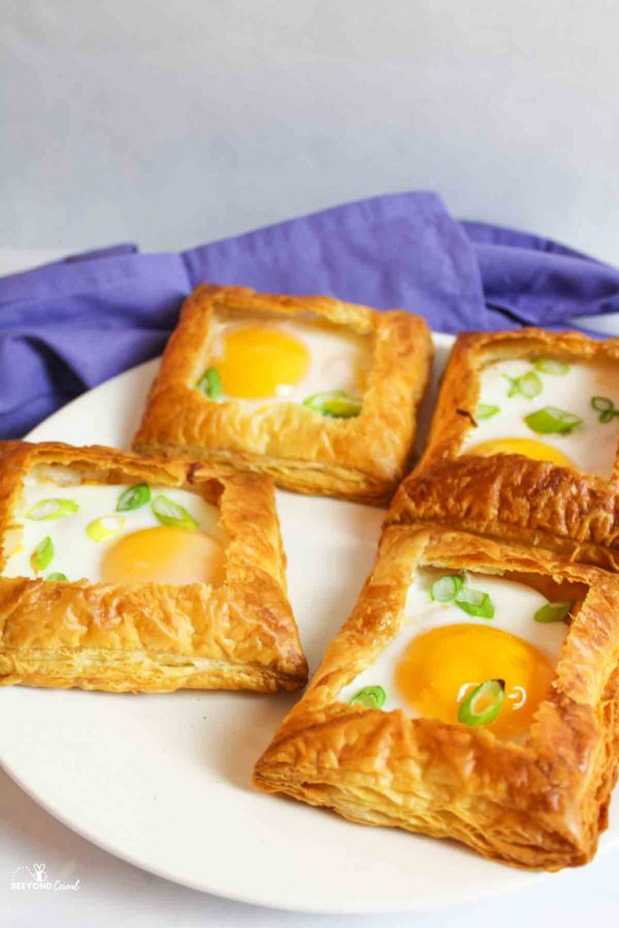 side view of 4 puff pastry egg tarts on a plate