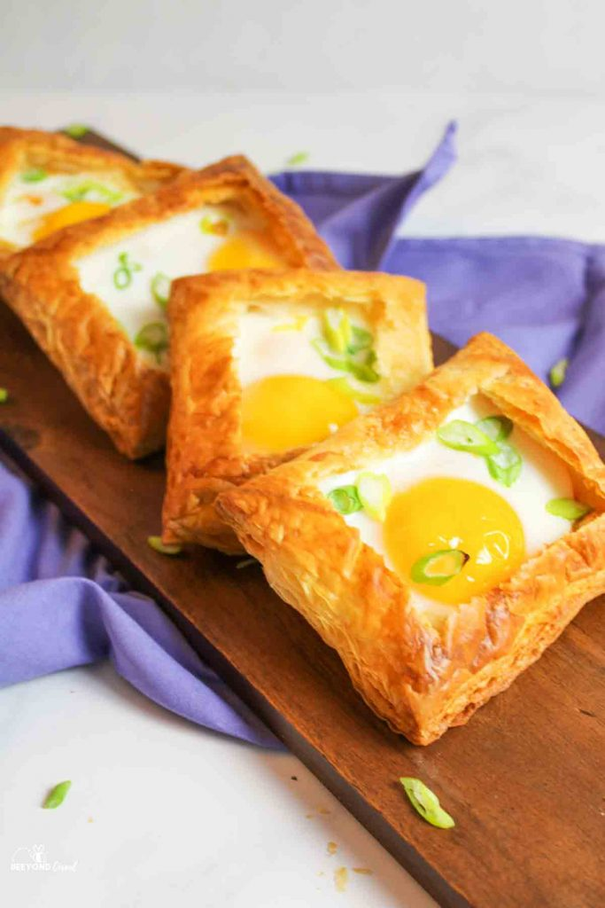 4 stacked and angled puff pastry egg tarts on a board