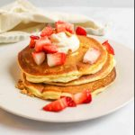 a stack of cheesecake pancakes with a dollop of cream cheese on top and diced strawberries scattered over the top