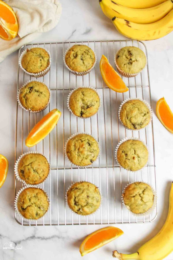 aerial view of a wire cooling rack filled with muffins and orange slices as well as ripe bananas aroun the tray