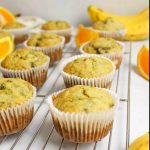 banana orange muffins on a wire cooling rack icely spaced and surrounded by orange slices and ripe bananas