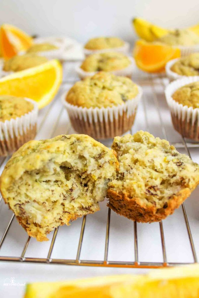 orange banana muffins on a wire cooling rck with fresh fruit and a muffin in front split in half to reveal soft inside