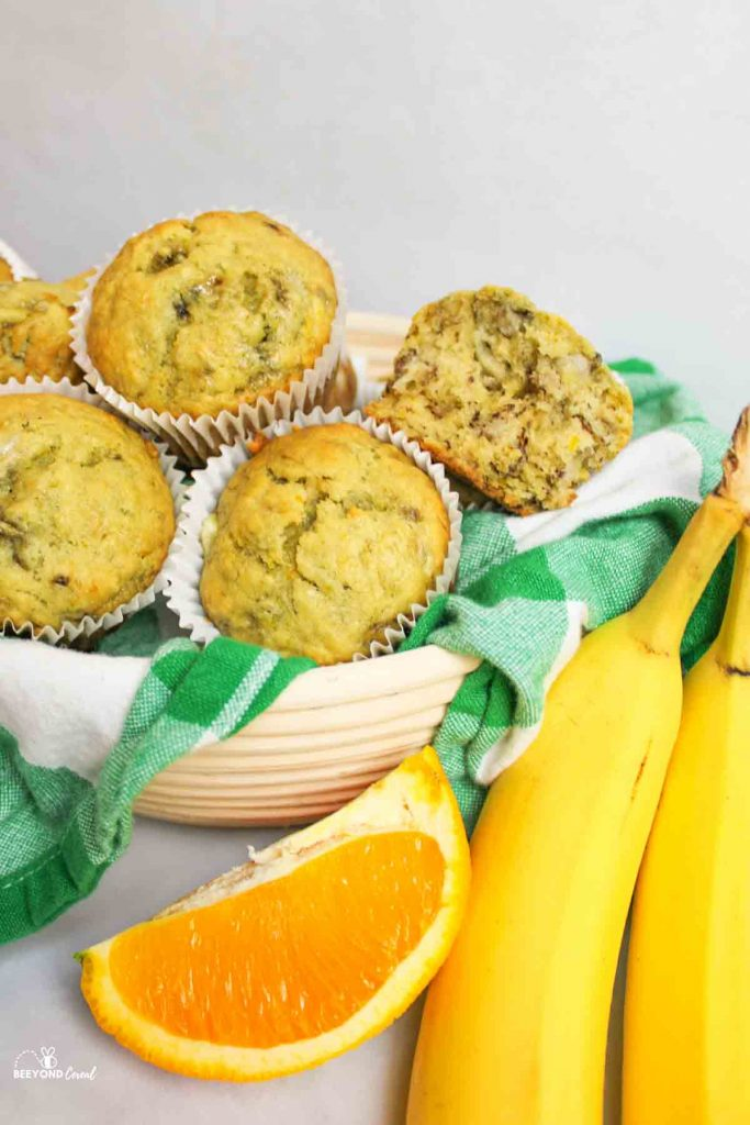 ripe bananas and an orange slice next to a green and white towel lined basket bowl filled with banana orange muffins