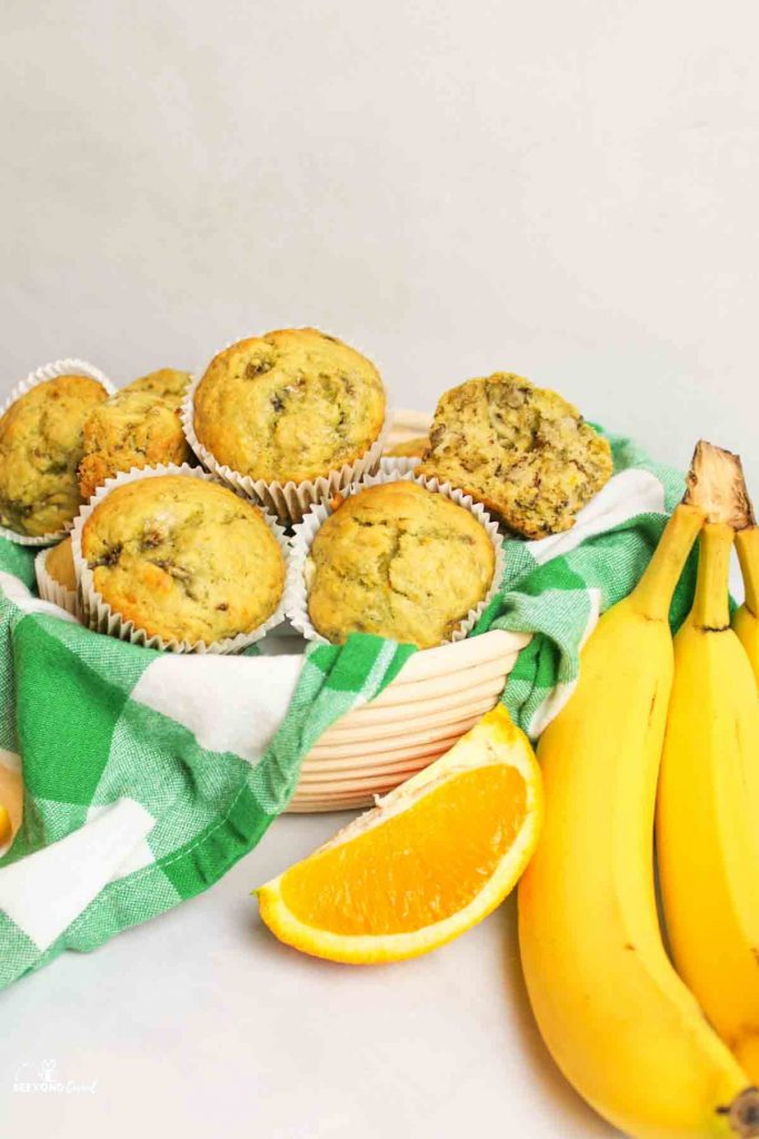 a basket with a green and white checkered towel filled with banana orange muffins and an orange slice and ripe bananas resting to the side