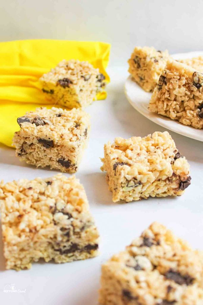a yellow towel in background with a white plate filled with chocolate chip rice krispie treats and several squares of treats arranged to the side