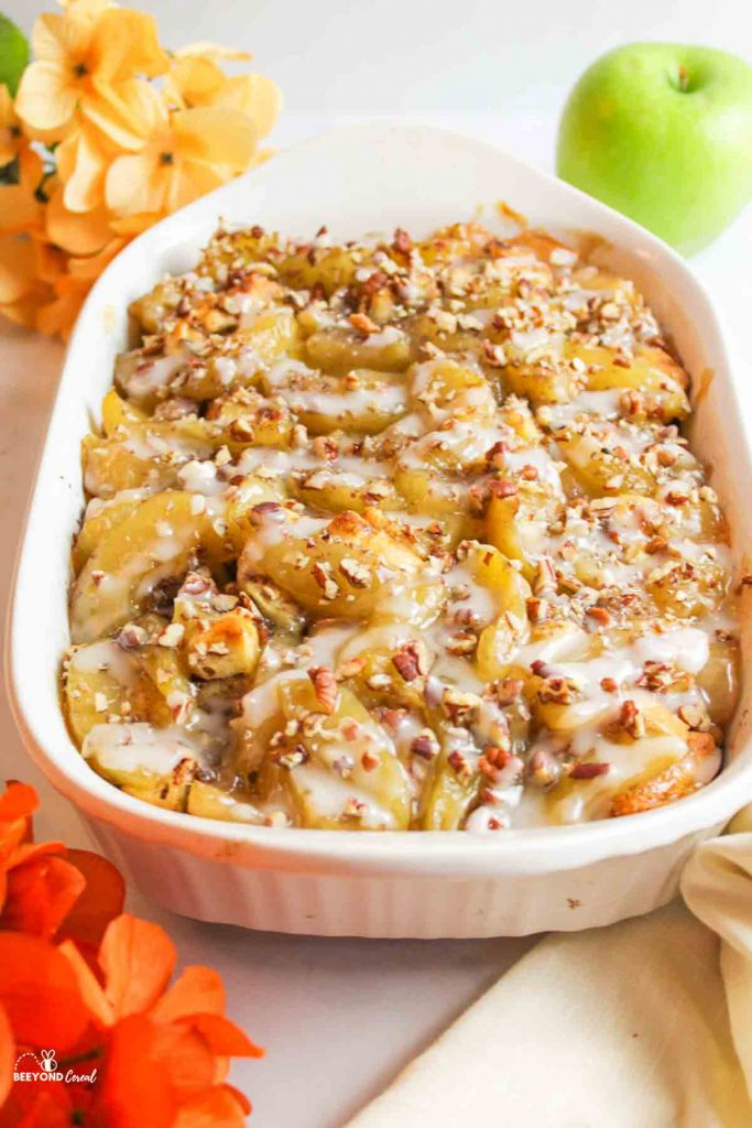 cinnamon roll apple cobbler in a white baking dish at the center of the screen with orange flowers in the left corners and a green apple in the far right corner and a towel in the nearest right corner