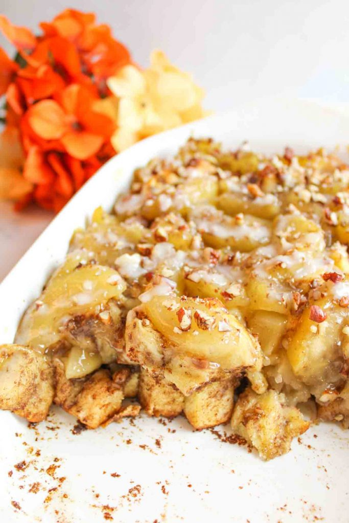 a cinnamon roll apple cobbler with servings missing and flowers in background