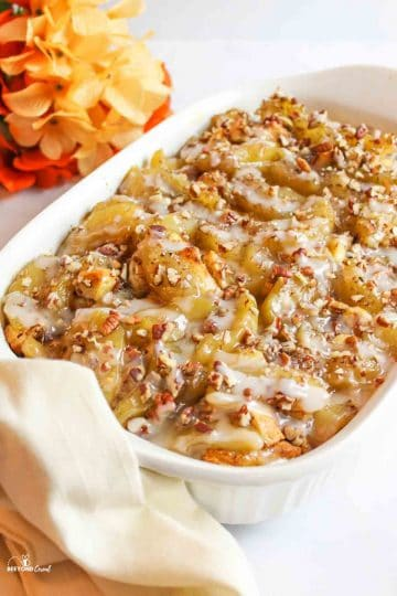 cinnamon roll apple cobbler in a white baking dish with orange flowers in background and a towel at one side of the baking dish