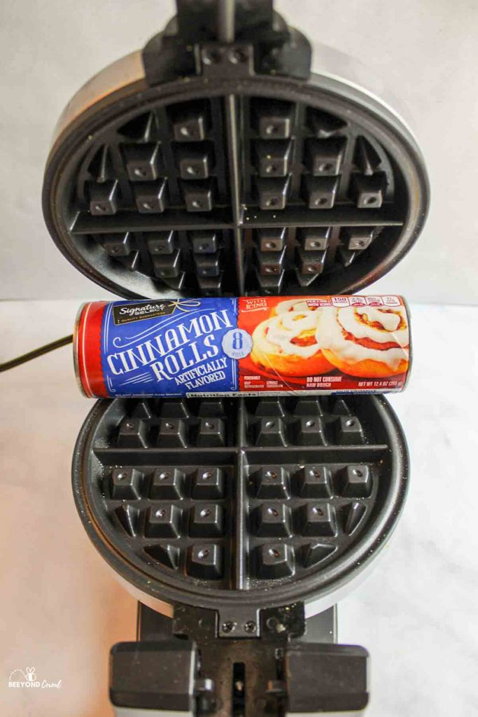 a can of cinnamon rolls inside of an opened waffle maker