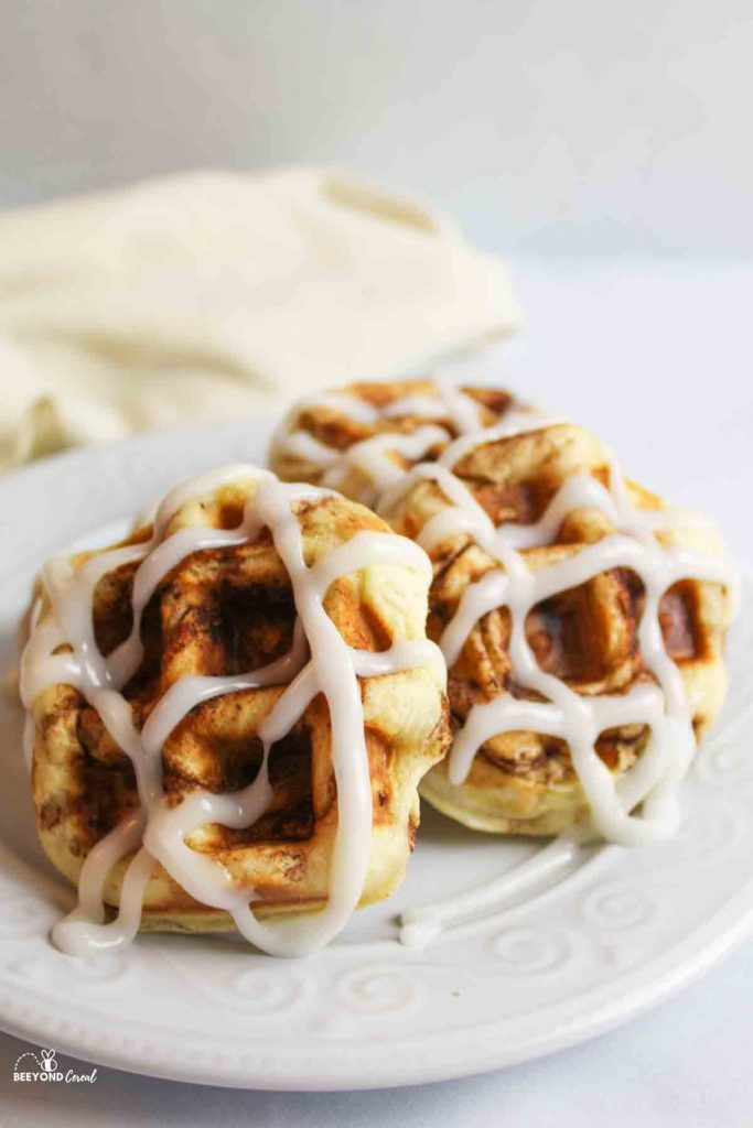 icing drizzled over cinnamon roll waffles on a plate