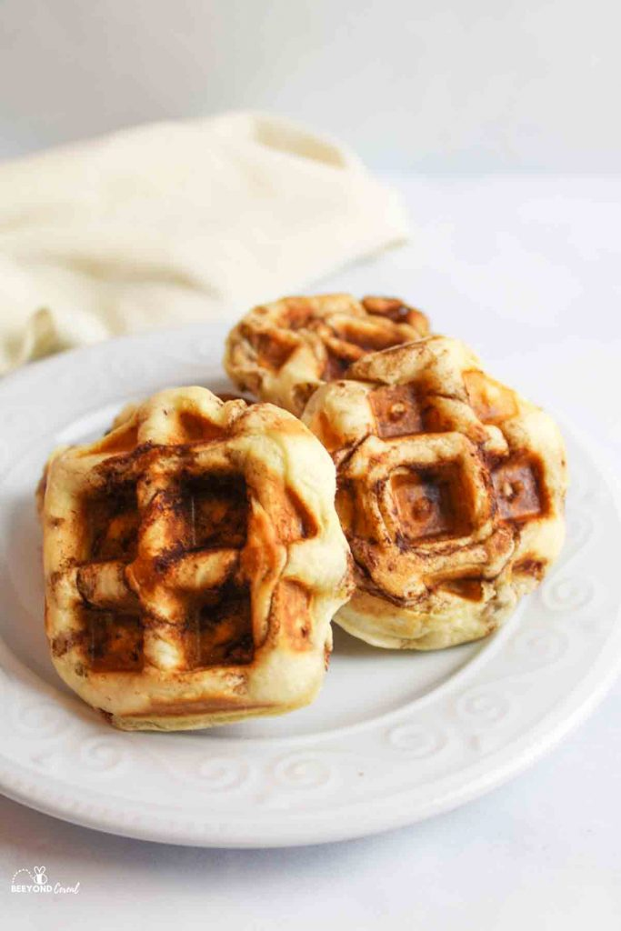 a small white plate with a pile of cinnamon roll waffles on it