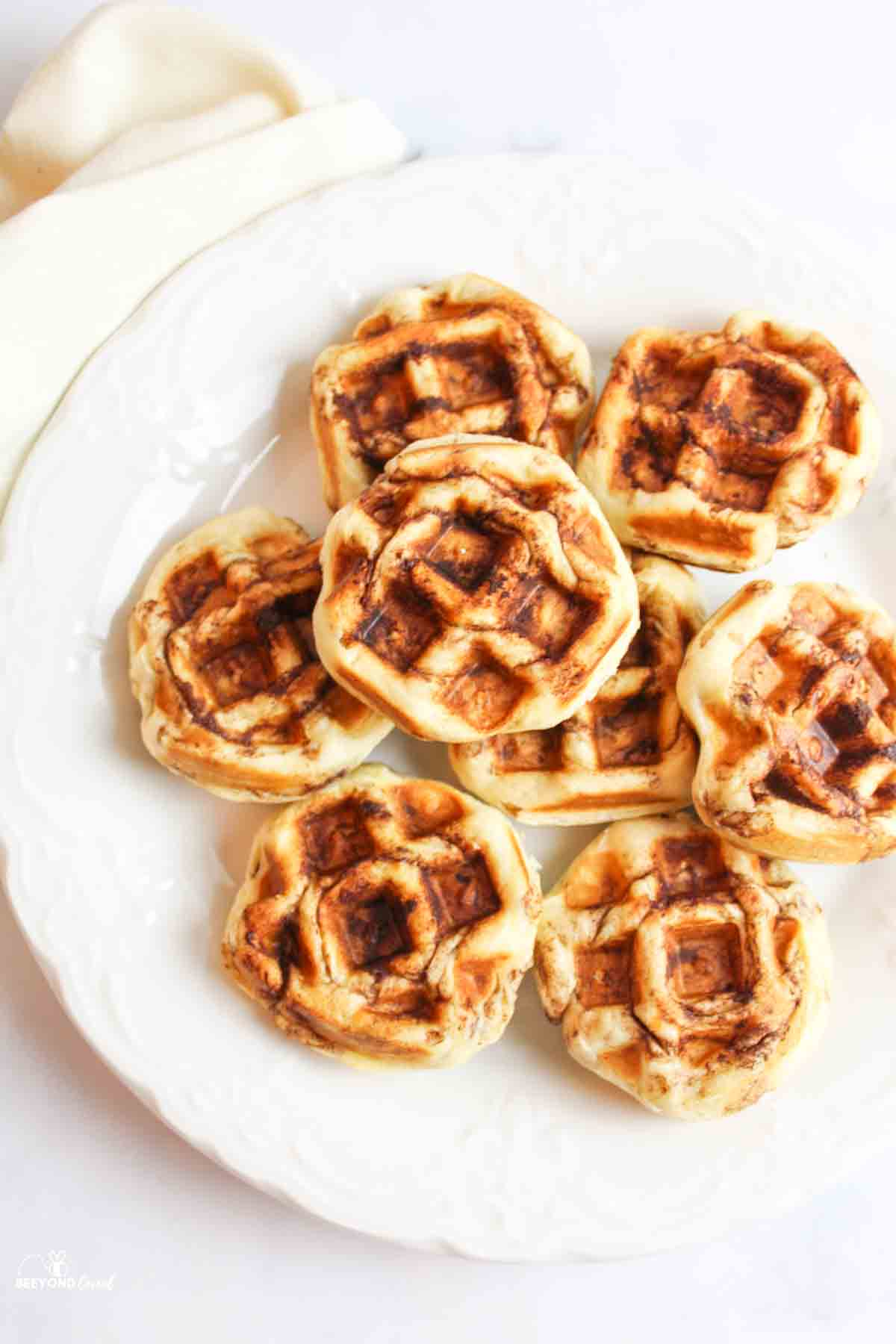 a white plate filled with cinnamon roll waffles