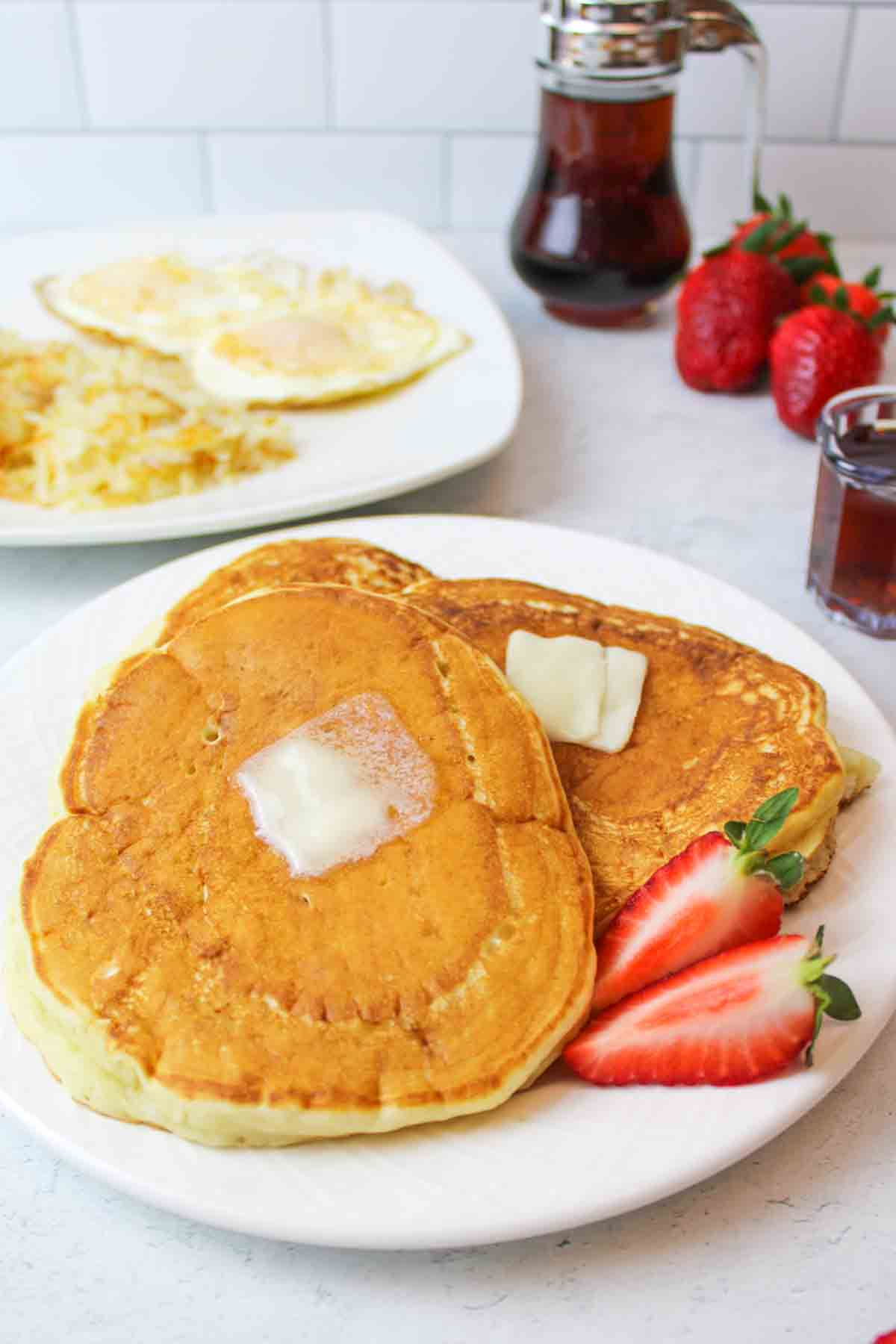 two large golden pancakes on a plate with egggs and hashbrowns