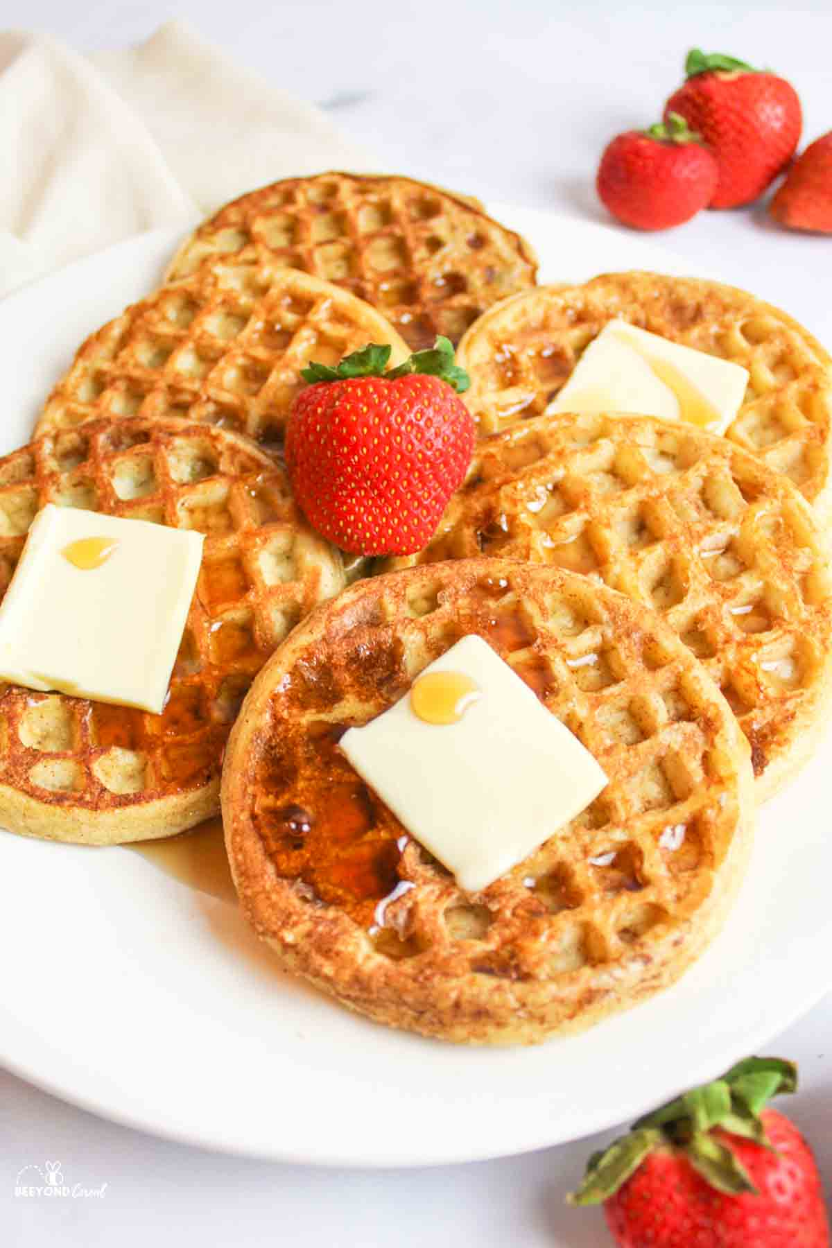 butter and syrup on a plate of waffles with a fresh strawaberry on top and to the sides